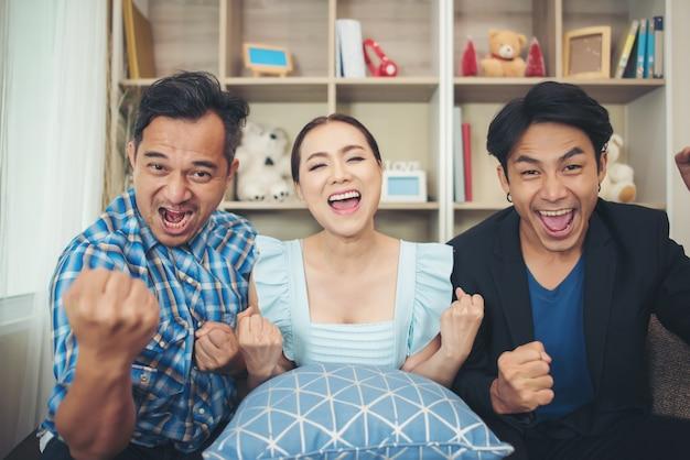 Três amigos estão felizes por assistir tv