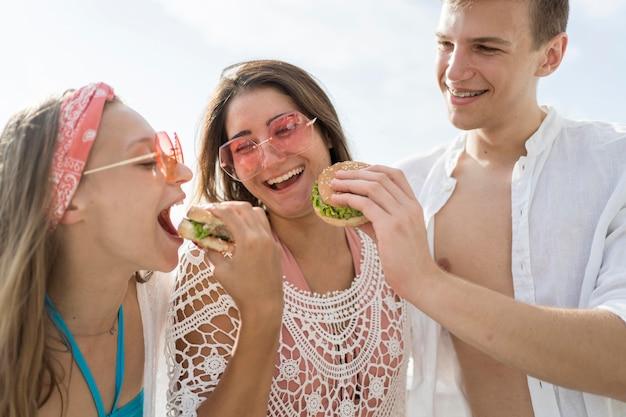 Três amigos felizes ao ar livre comendo hambúrgueres juntos