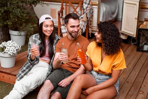 Três amigos felizes bebendo ao ar livre