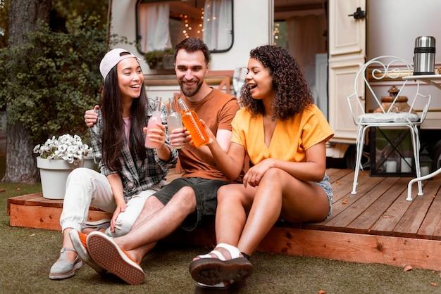 Três amigos felizes bebendo e sorrindo