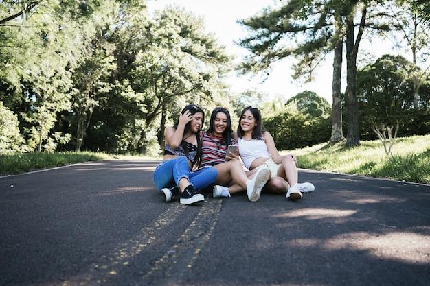 Três amigos felizes compartilhando redes sociais em um smartphone ao ar livre em um parque