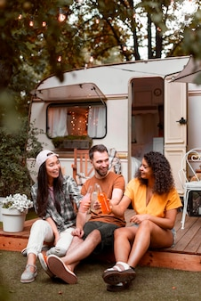 Três amigos felizes na frente da van