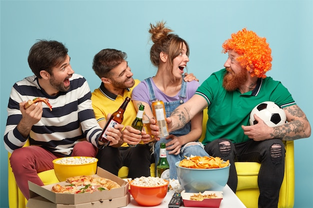 Três amigos felizes olham para um homem barbudo engraçado de peruca, tilintam garrafas de cerveja, comem pizza e se divertem enquanto assistem a um jogo de futebol na televisão