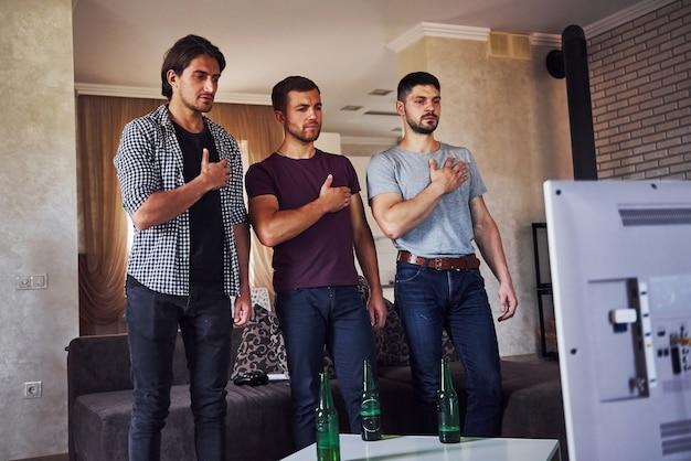 Três amigos fica dentro de casa contra a tv com as mãos no coração. tocando um hino nacional.