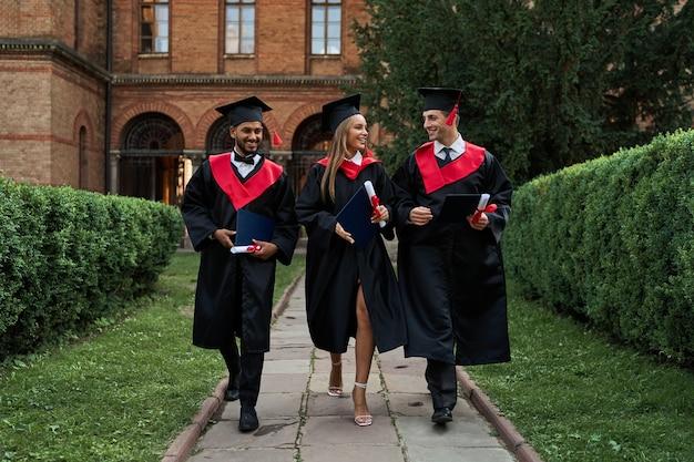 Três amigos graduados em vestidos de formatura caminhando pelo campus.