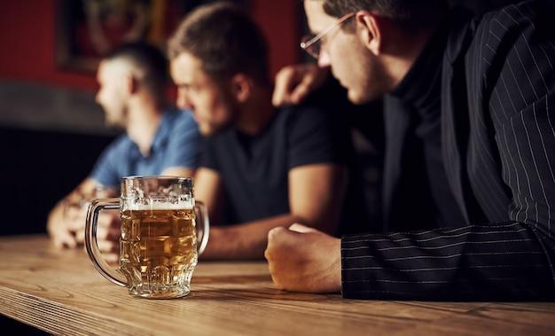 Três amigos homens no bar