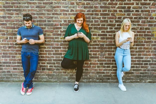 Três amigos, inclinar-se, um, parede, digitando, ligado, seu, telefones