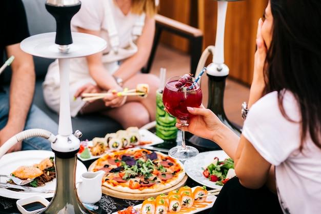 Três amigos jantando com salada de pizza de sushi e cachimbo de água