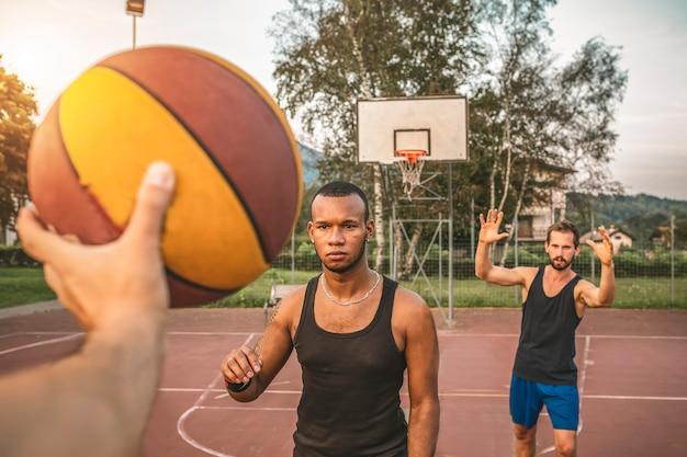 Três amigos jogam basquete. close do passe de basquete