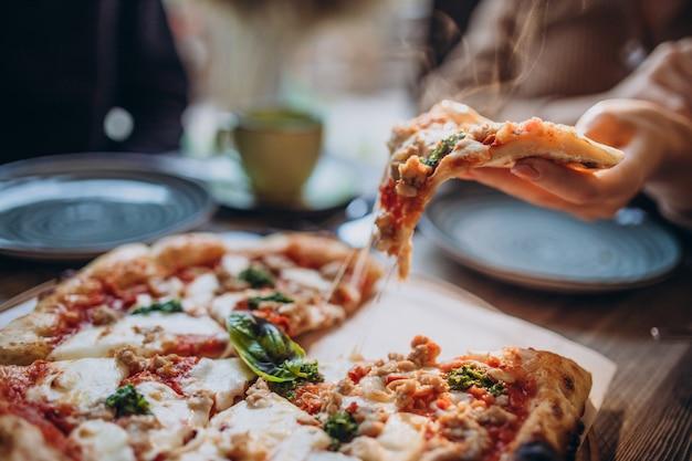 Três amigos juntos comendo pizza em um café