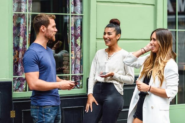 Três amigos multiétnicas pessoas rindo ao ar livre