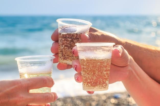 Três amigos na praia estão bebendo vinho espumante