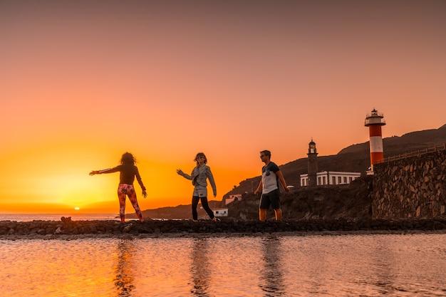Três amigos no pôr do sol laranja nas salinas e ao fundo o farol de fuencaliente na rota dos vulcões ao sul da ilha de la palma, nas ilhas canárias, espanha