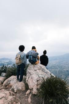 Três amigos no topo da montanha olhando a vista