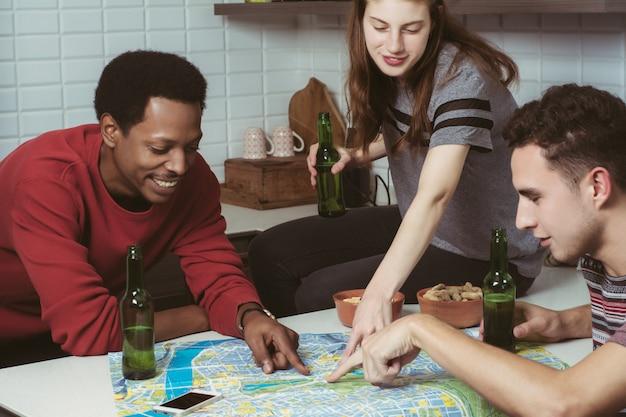 Três amigos planejando uma viagem em casa.
