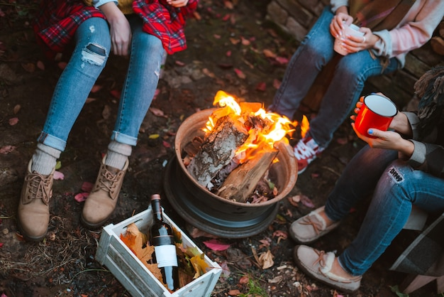 Três amigos relaxam confortavelmente e bebem vinho em uma noite de outono ao ar livre perto da lareira no quintal