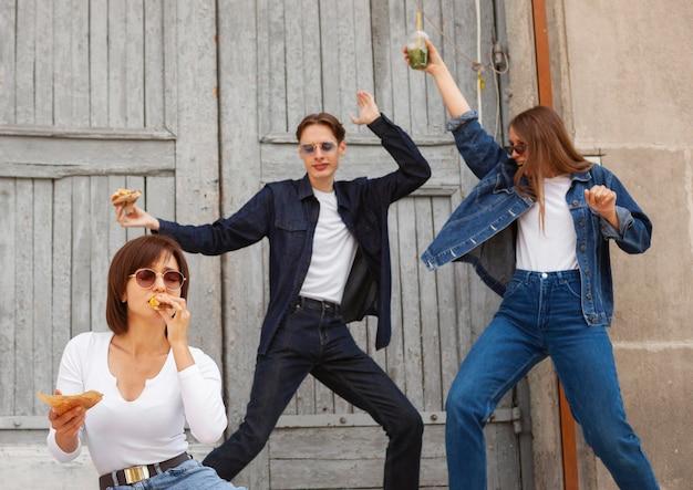 Três amigos se divertindo ao ar livre enquanto comem hambúrguer