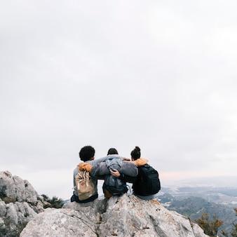 Três amigos sentados no topo da montanha, apreciando a vista