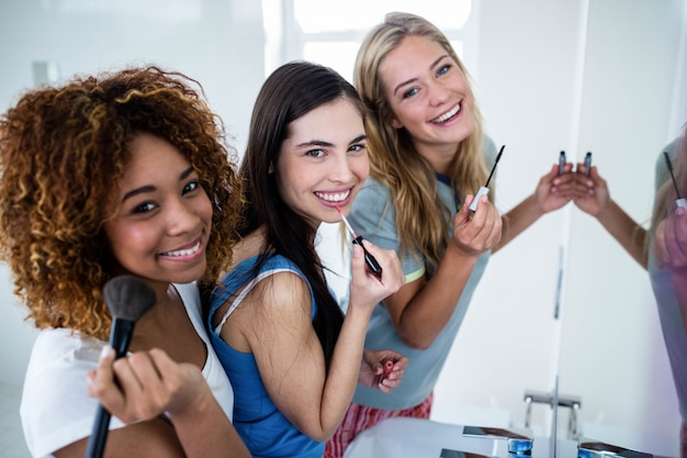 Três amigos sorridentes colocando maquiagem juntos no banheiro