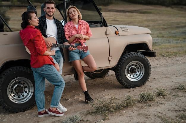 Três amigos sorridentes tocando violão enquanto viajam de carro