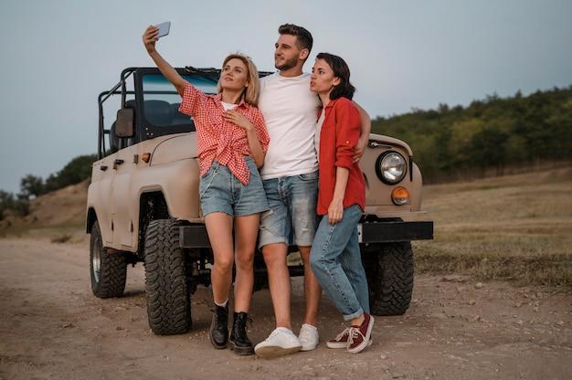 Três amigos tirando selfie com smartphone enquanto viajam de carro
