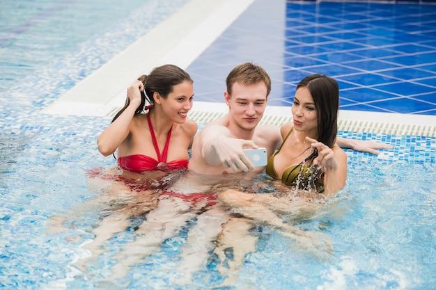 Três amigos tomando selfie na piscina. conceito sobre amizade, pessoas, tecnologia e diversão
