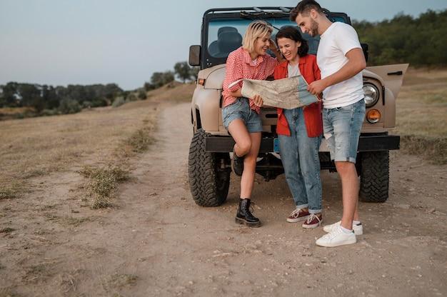 Três amigos verificando o mapa enquanto viajam de carro juntos