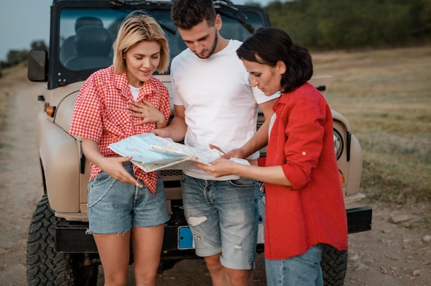 Três amigos verificando o mapa enquanto viajam de carro