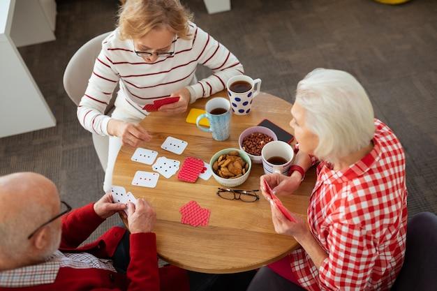 Três amigos. vista superior de pessoas idosas e felizes sentadas ao redor da mesa redonda