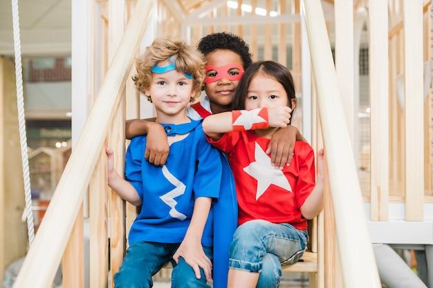 Três amiguinhos afetuosos fantasiados sentados na escada enquanto passam o tempo na área de recreação do quarto das crianças