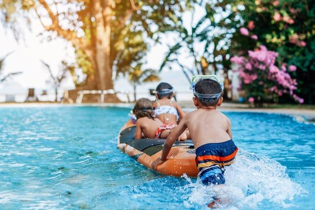 Três amiguinhos em trajes de banho com óculos de proteção nadando em um barco e curtindo suas férias na tailândia.