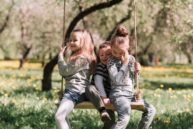 Três amiguinhos sentados em um balanço no jardim em um dia de primavera. o conceito de uma infância feliz