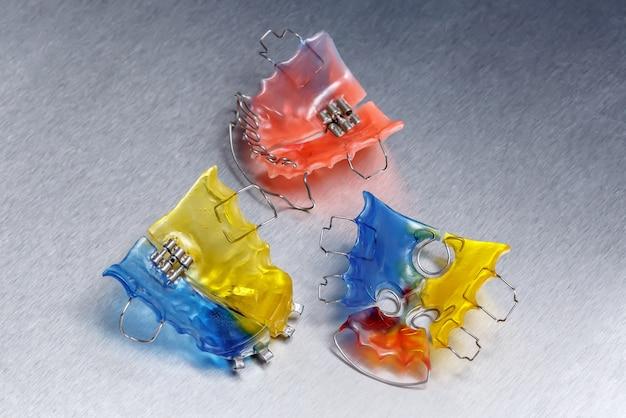 Três aparelhos dentários coloridos ou retentores para dentes na parede de metal