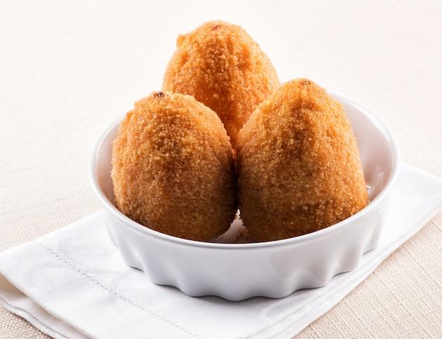Três arancini frito profundo da sicília em uma tigela
