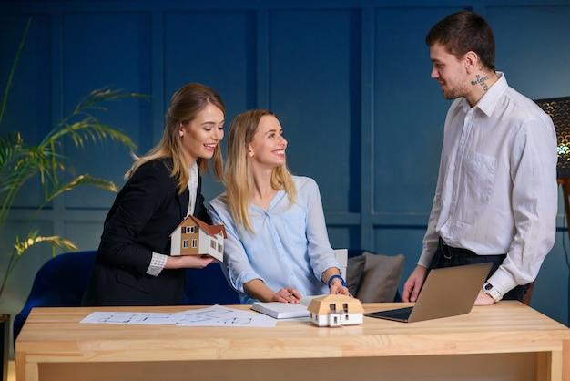 Três arquitetos discutindo o projeto da casa nova, plana.