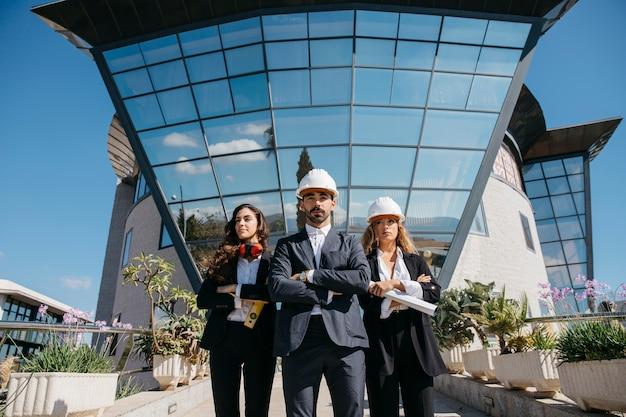 Três arquitetos em frente ao prédio com grandes janelas