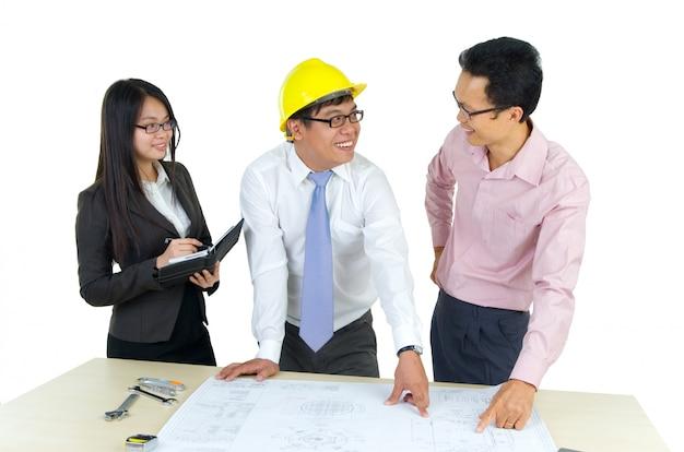 Três arquitetos em pé na frente da mesa e discutindo sobre a papelada.