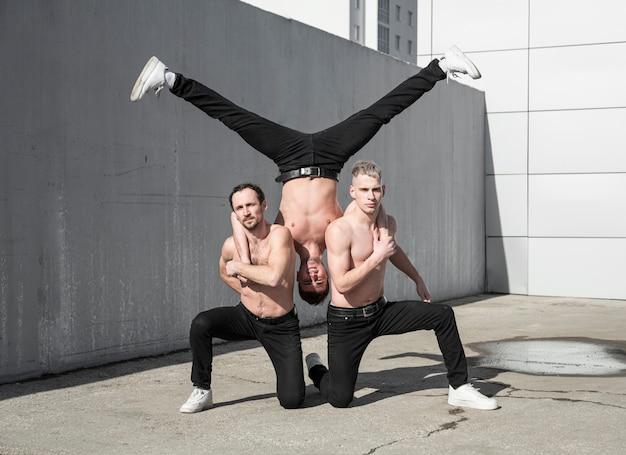 Três artistas de hip hop sem camisa praticando uma pose