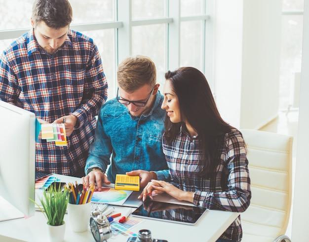 Três artistas designers criativos trabalhando no computador no escritório
