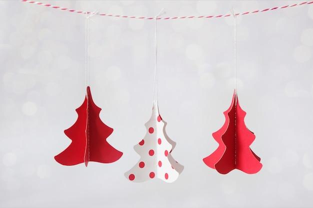 Três árvores de natal feitas de papel em vermelho e branco