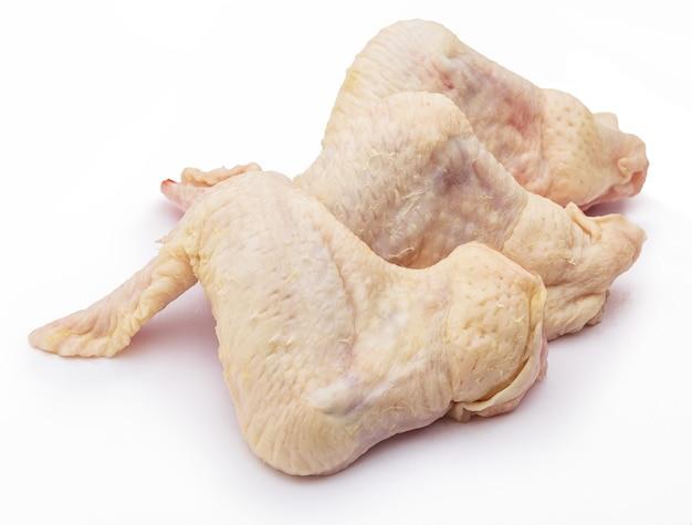 Três asas de frango limpas e crus, isoladas no fundo branco.