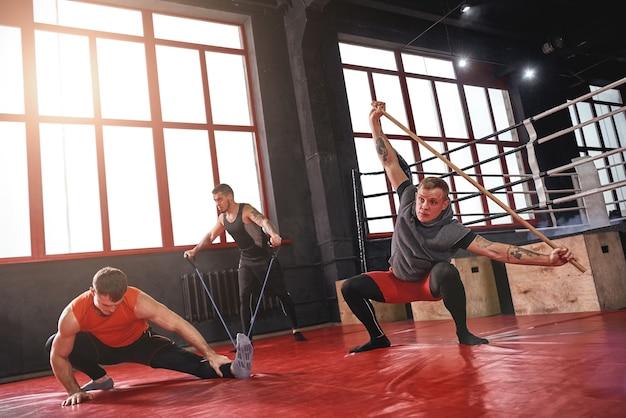 Três atletas musculosos focados em roupas esportivas coloridas, alongamento com diferentes equipamentos esportivos antes de um treino pesado na academia de boxe