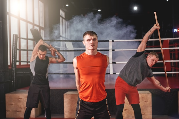 Três atletas musculosos focados em roupas esportivas coloridas, olhando para a câmera enquanto se alongam, antes de um treino pesado na academia de boxe