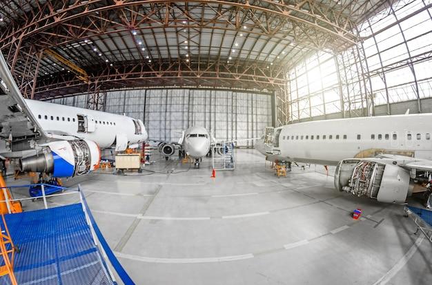 Três aviões de passageiros na manutenção do motor e reparação da fuselagem no hangar do aeroporto.