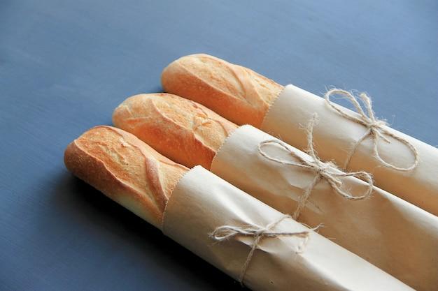 Três baguetes francesas em embalagens de papel estão sobre um fundo escuro