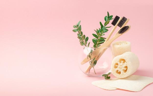 Três bambu, escovas de madeira em um copo de vidro em um fundo rosa. toalhas de bucha. copie o espaço. medicina conceitual, zero desperdício, reciclagem