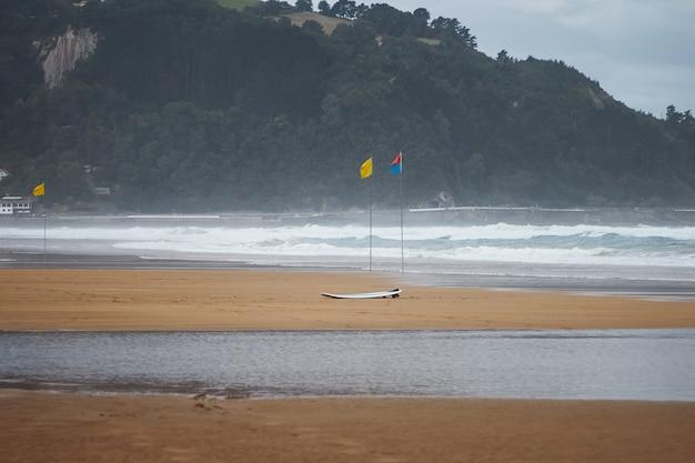 Três bandeiras de praia coloridas e uma prancha de surf em uma praia ventosa sob colinas verde-escuras