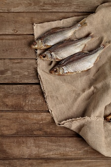 Três baratas secas ao ar salgadas em pano de saco com fundo de madeira