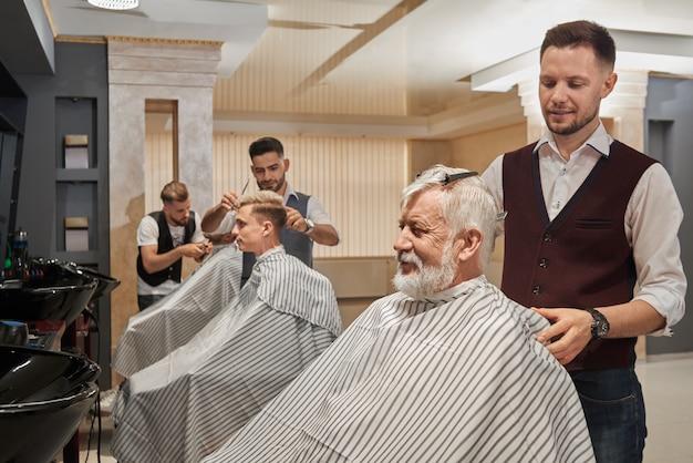 Três barbeiros cortando e arrumando os cabelos dos clientes.