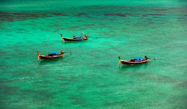 Três barcos flutuam no mar esmeralda verde claro, com vista para o recife de coral subaquático.